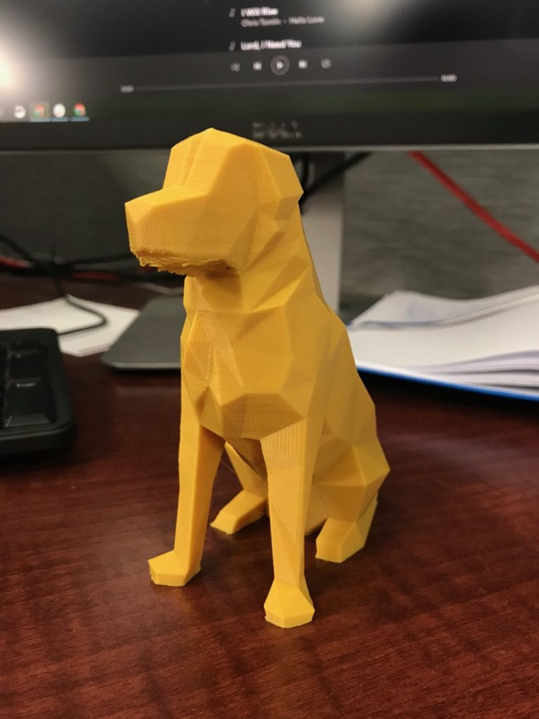 A yellow 3D printed dog on a desk